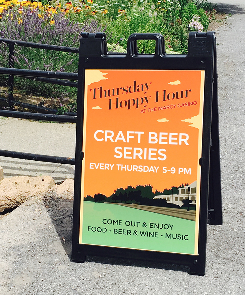 A double-sided A Frame sign placed outside of the Marcy Casino advertises their weekly Hoppy Hour event