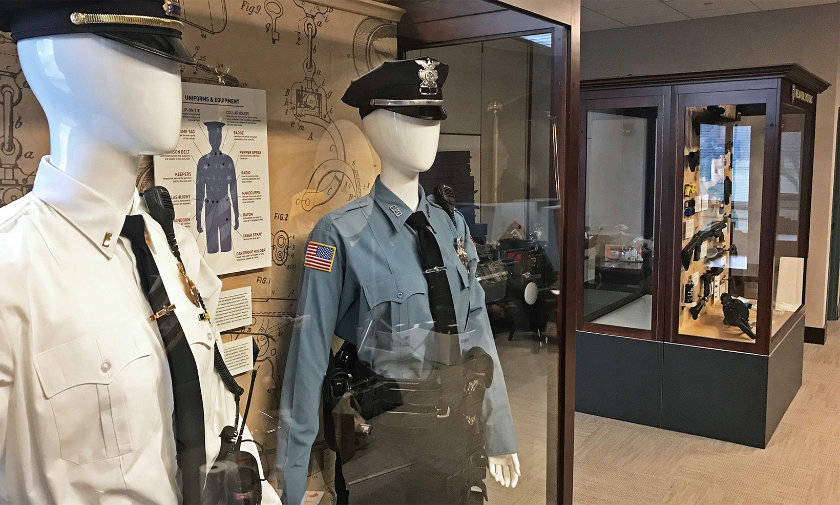 The beginnings of the Cheektowaga PD law enforcement museum, consisting of two display cases arranged with uniforms and firearms
