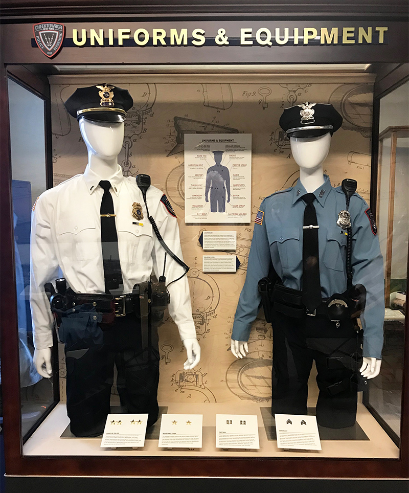 A display case shows the uniforms and equipment used by the Cheektowaga Police Department, including a diagram to show the location of each item on mannequins