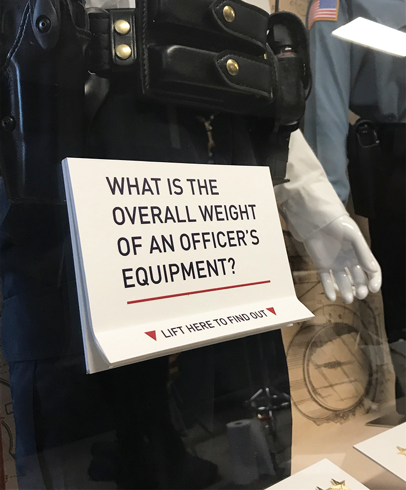 A flip up trivia card on the front of the Uniforms & Equipment display case allows viewers to interact with exhibit