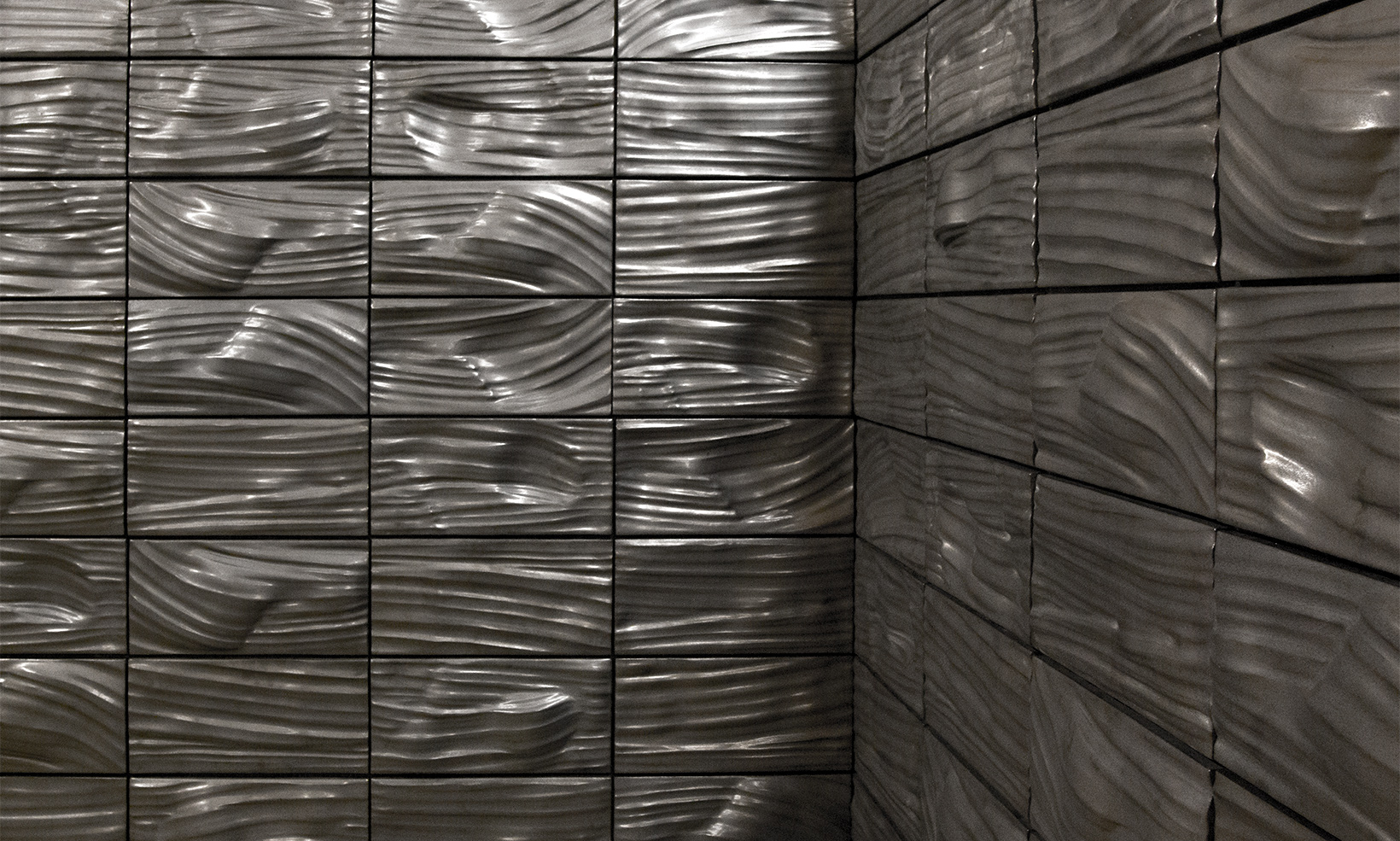Ceramic artist Anne Currier's exhibit 'Display' consists of a series of undulating terra cotta tiles glazed in both black and white