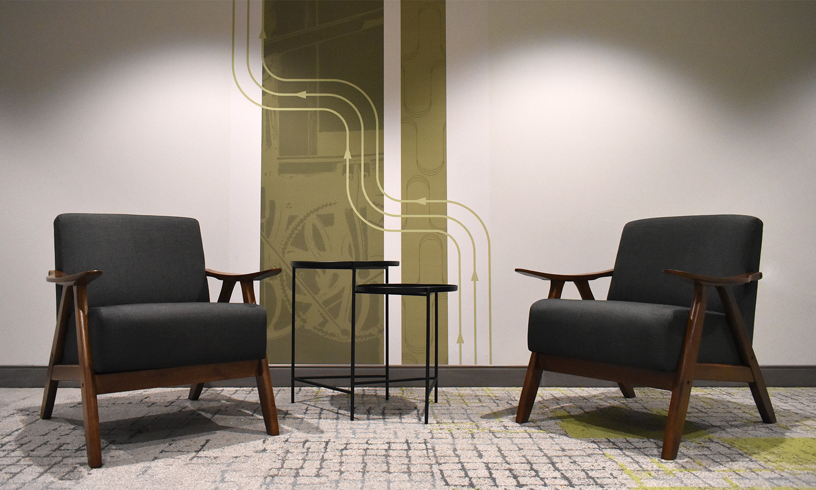 Two armchairs selected for a Forge Apartments common room work with the wall graphics to support the building's overall aesthetic and brand