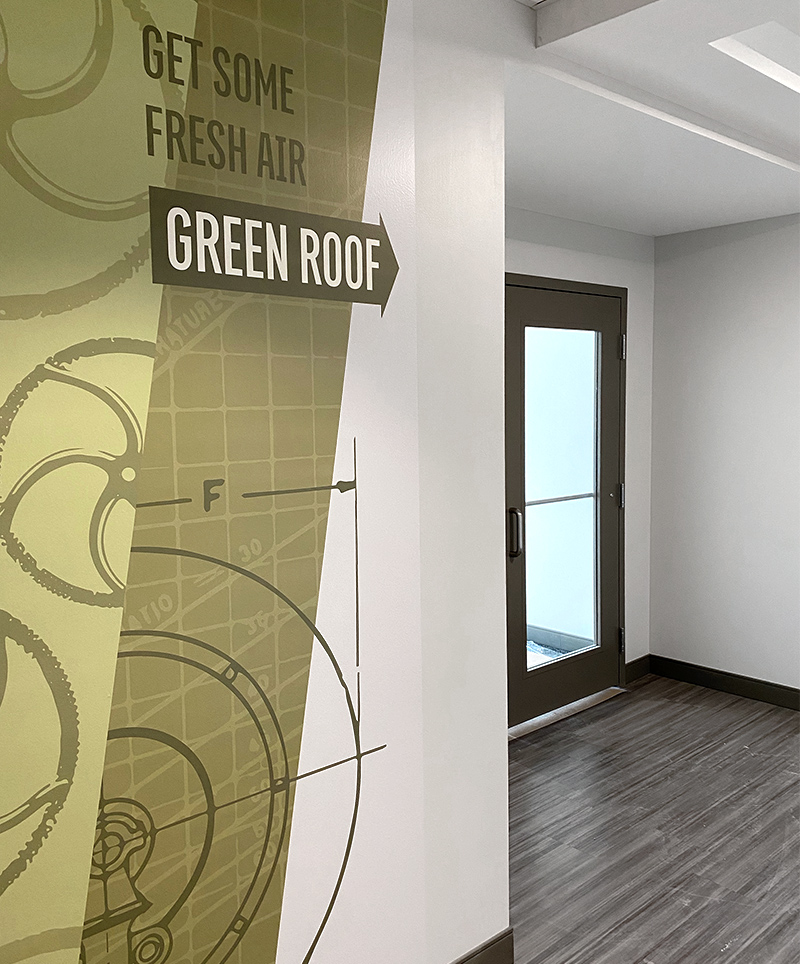A wall mural in shades of green leads visitors and tenants to the outdoor green roof at the Forge on Broadway