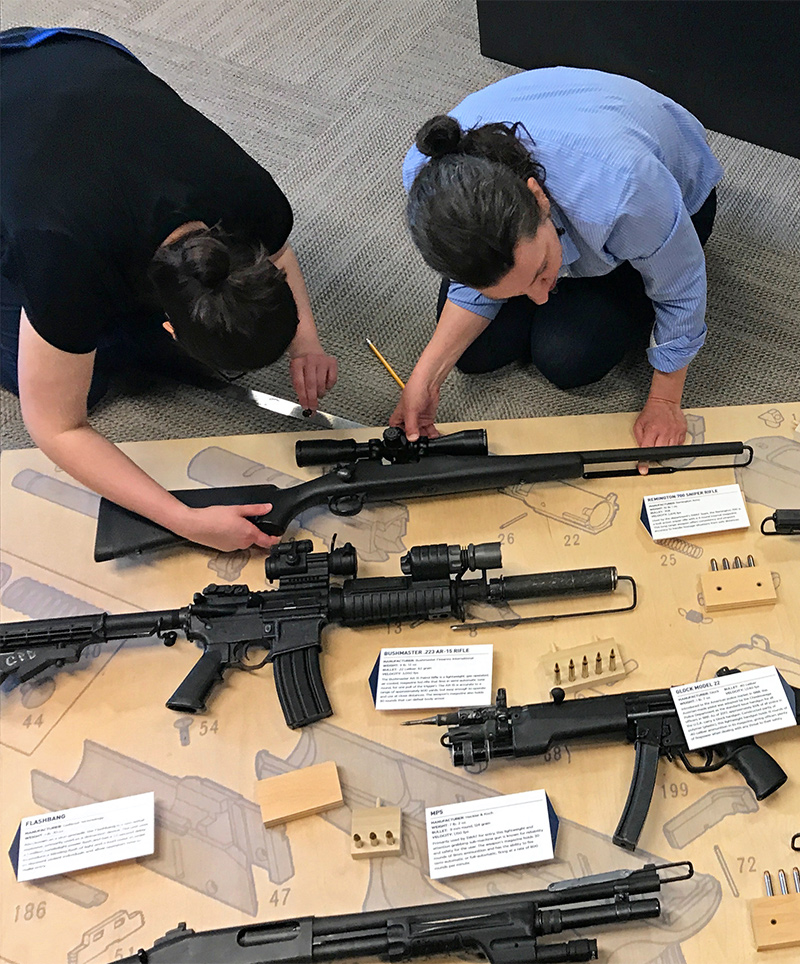 The OWEN team works on finalizing the backboard layout on the CPD Firearms Exhibit
