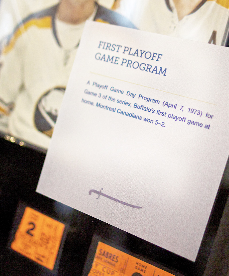 An information panel informing viewers on the Buffalo Sabres' first playoff game accompanies a display case in the Forging A Connection exhibit