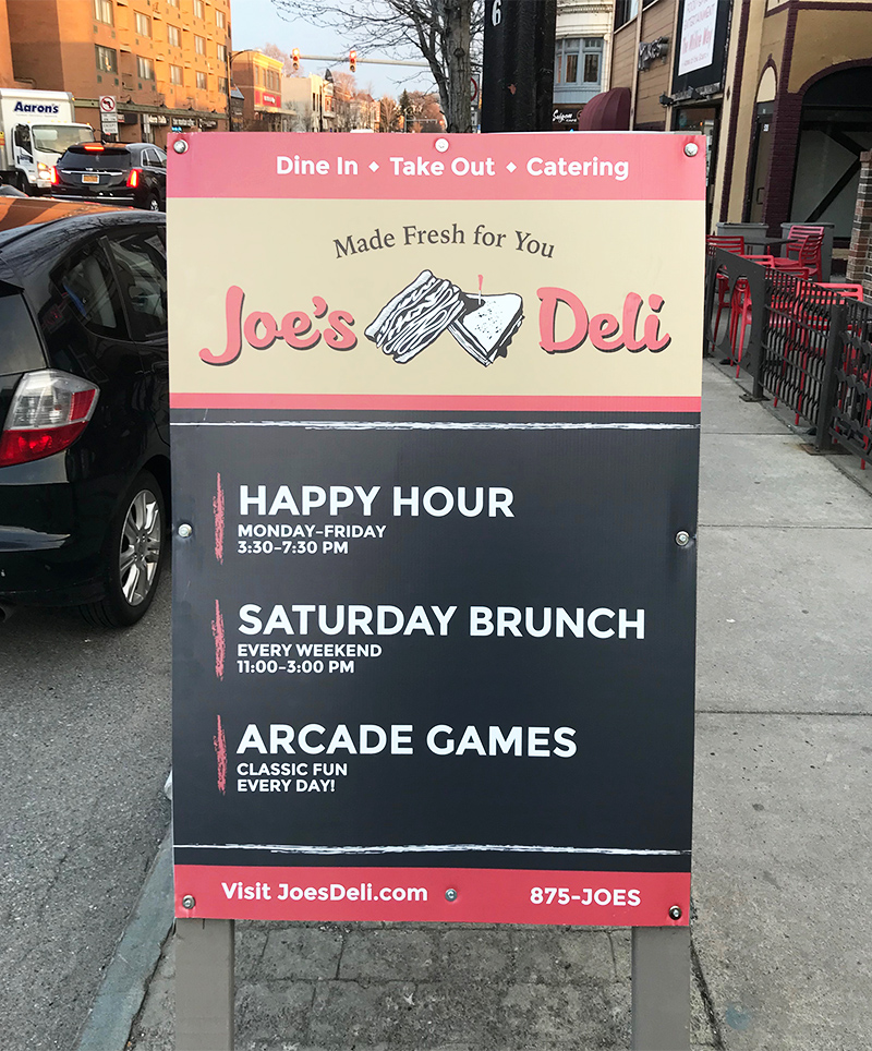 A double-sided A frame sign is displayed in front of Joe's Deli, advertising events such as happy hour and brunch