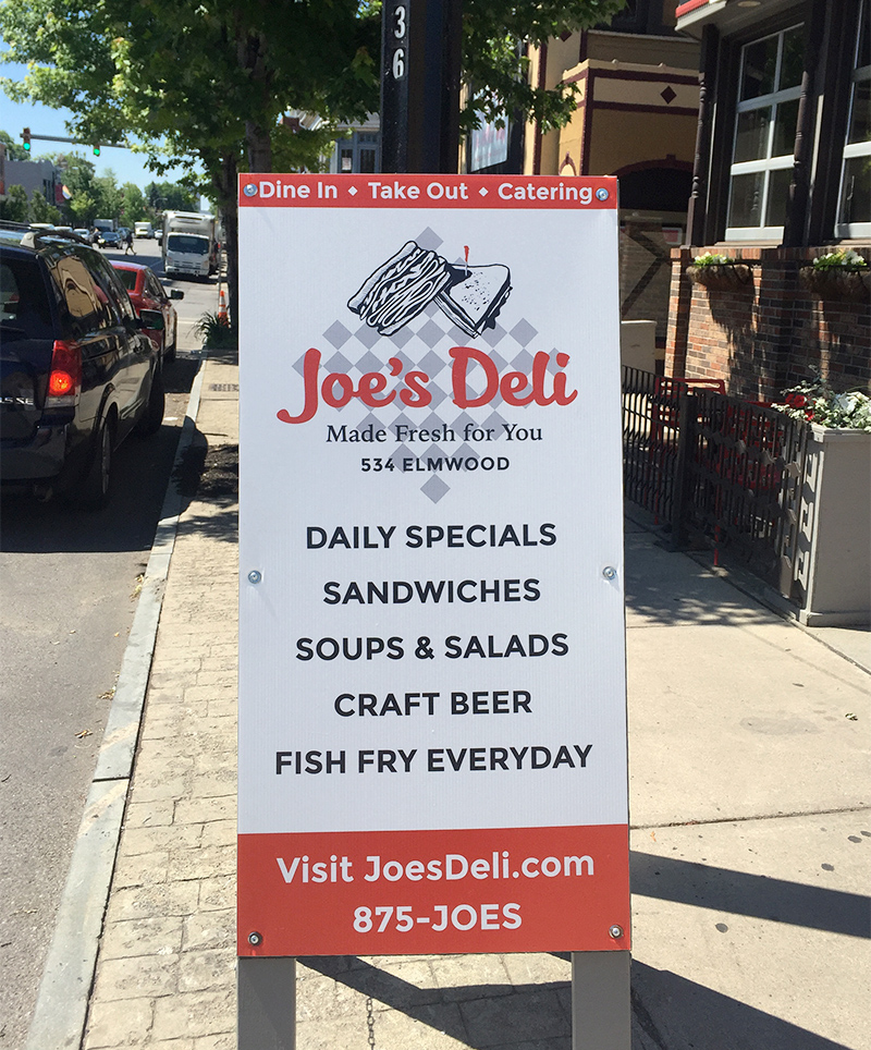 An outdoor A-frame sign sits on the sidewalk in front of Joe's Deli, advertising their offerings to pedestrians