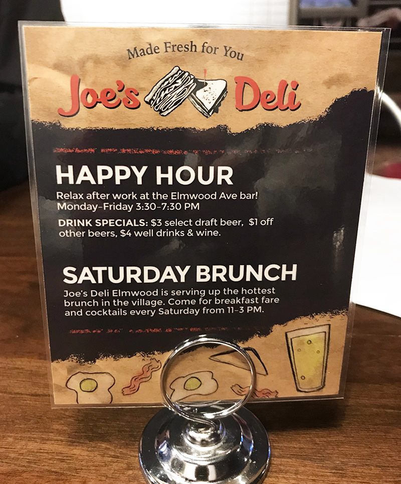A small tabletop display advertising the Joe's Deli drink and brunch specials creates an additional marketing touchpoint for diners