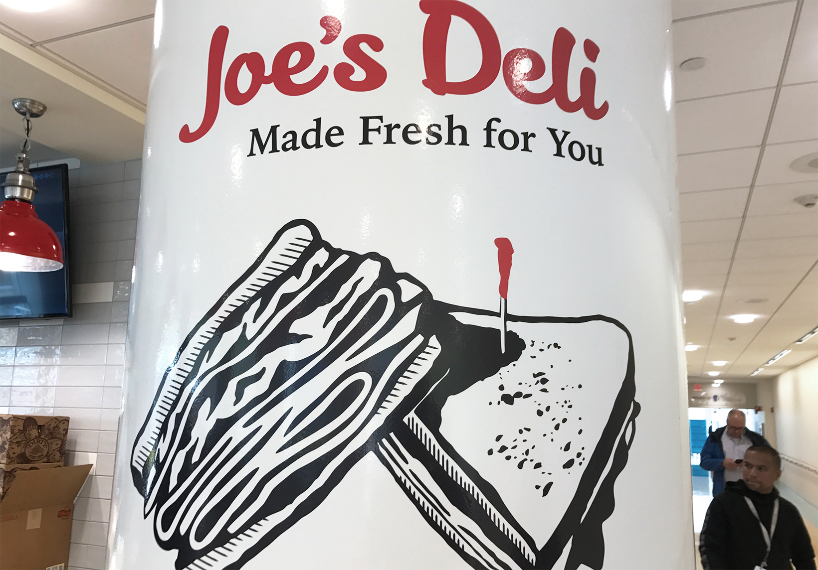 OW|EN designed an indoor column wrap for the Joe's Deli Oishei location, featuring a large scale version of their sandwich logo