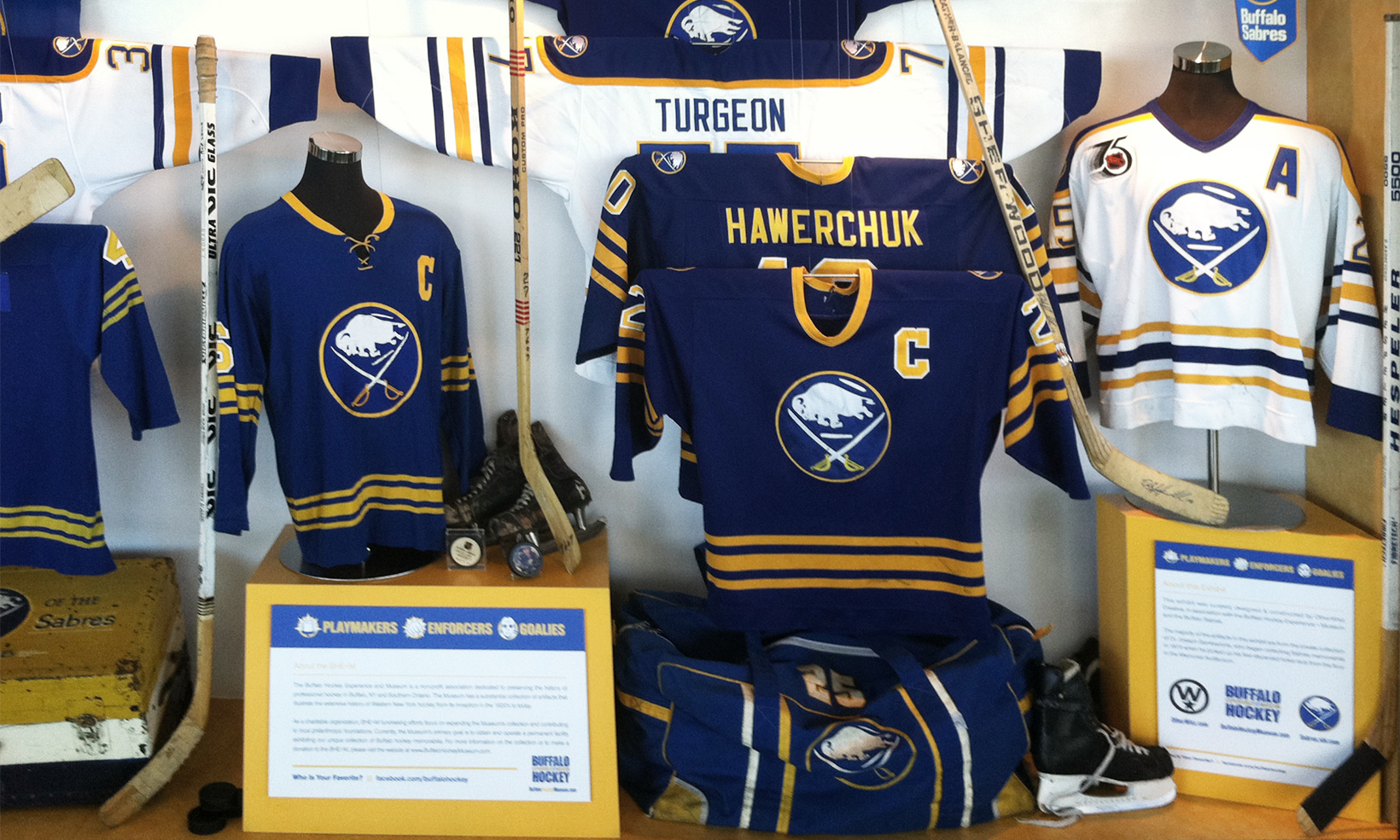The Playmakers, Enforcers, & Goalie's exhibit tells a narrative through the arrangement of Sabres' hockey jerseys and sticks