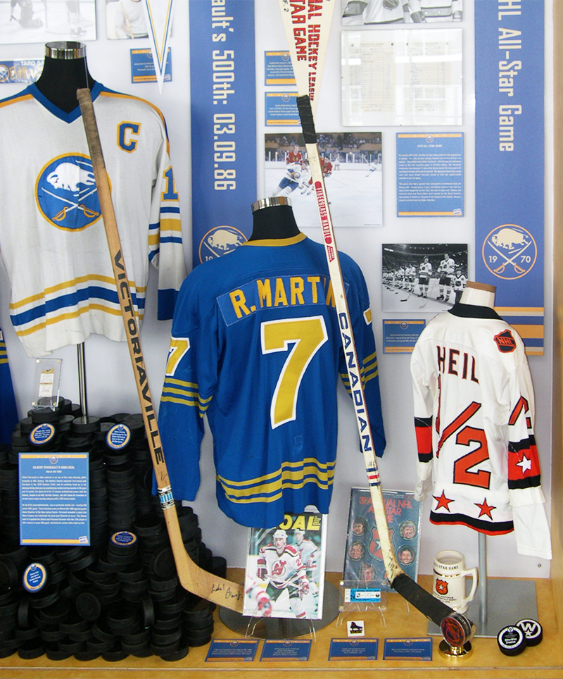 Vintage hockey sticks and jerseys used by Buffalo Sabres players comprise the exhibit display for the Sabres' 40th Anniversary