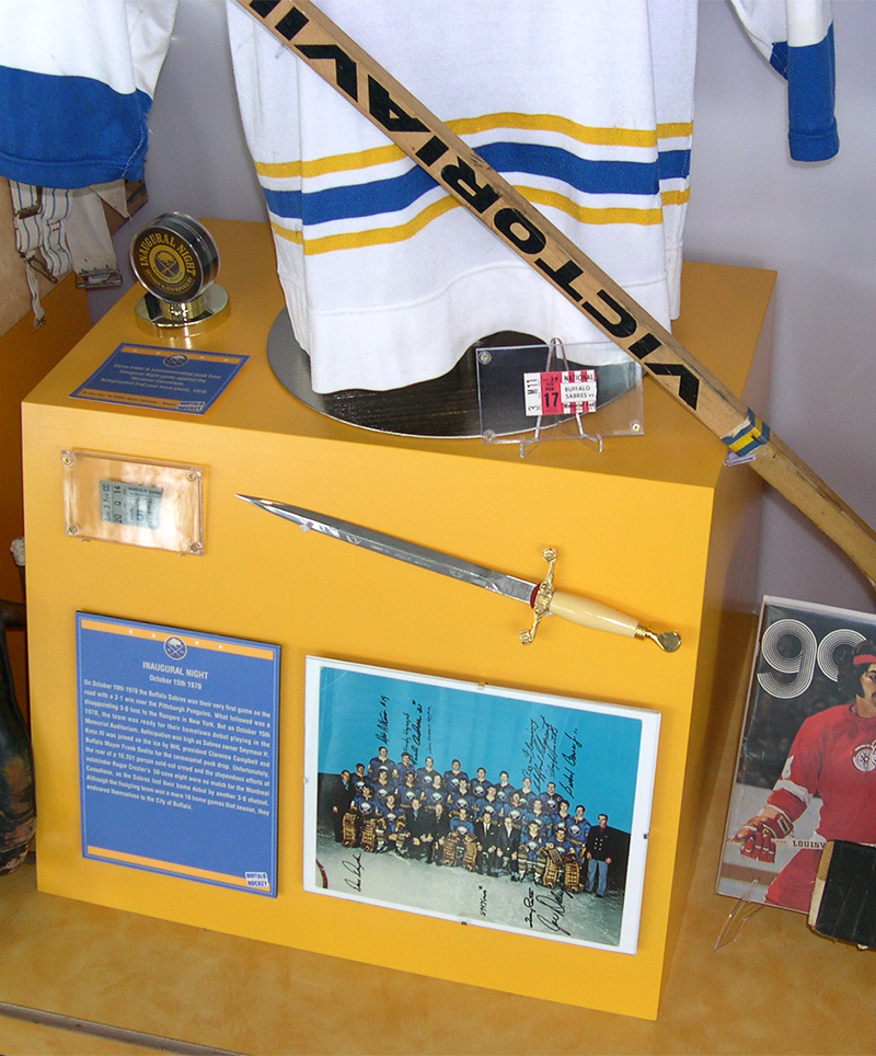 A detail shot of the Sabres 40th Anniversary exhibit display, showcasing artifacts, photos, and ticket stubs from an Inaugural Night